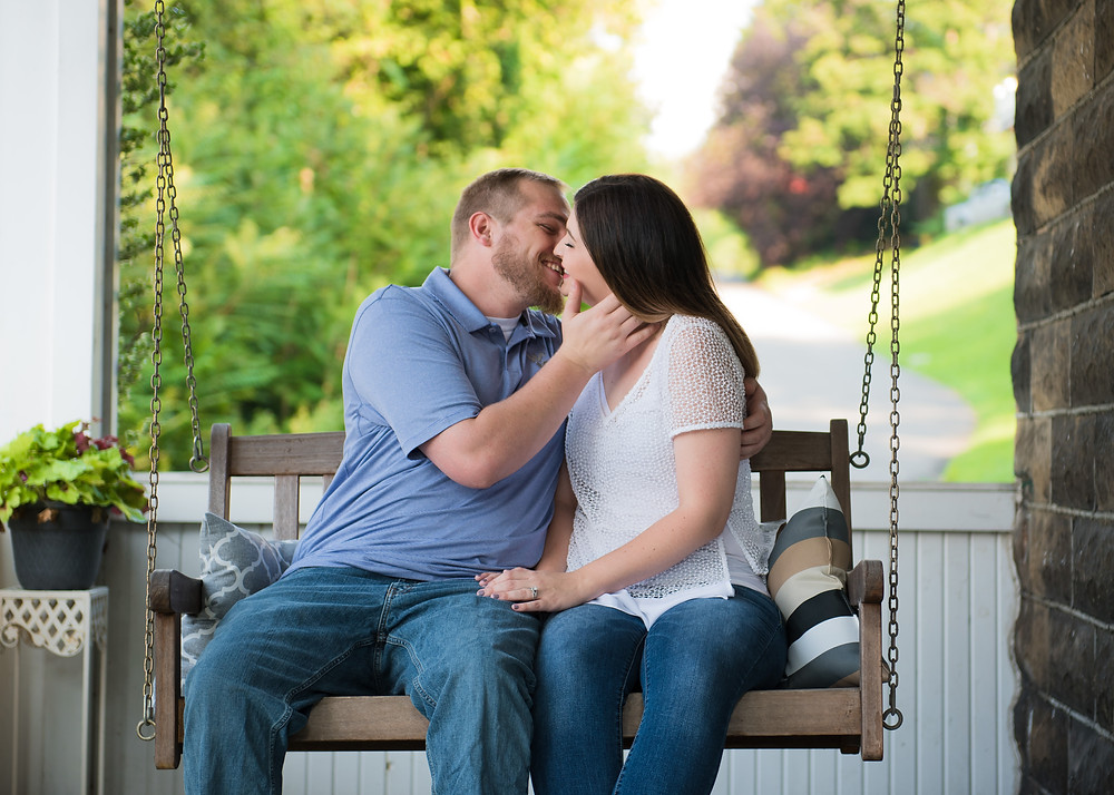 Engaged couple leaning in for a kiss on a porch swing in Morgantown, WV.