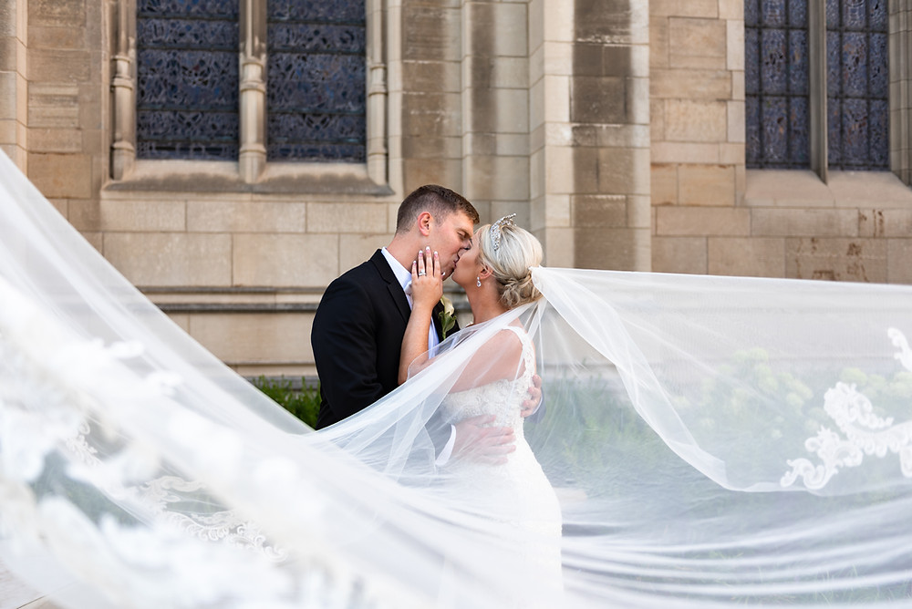 Bride and groom kissing while the veil flies in the wind; Pittsburgh wedding photographer