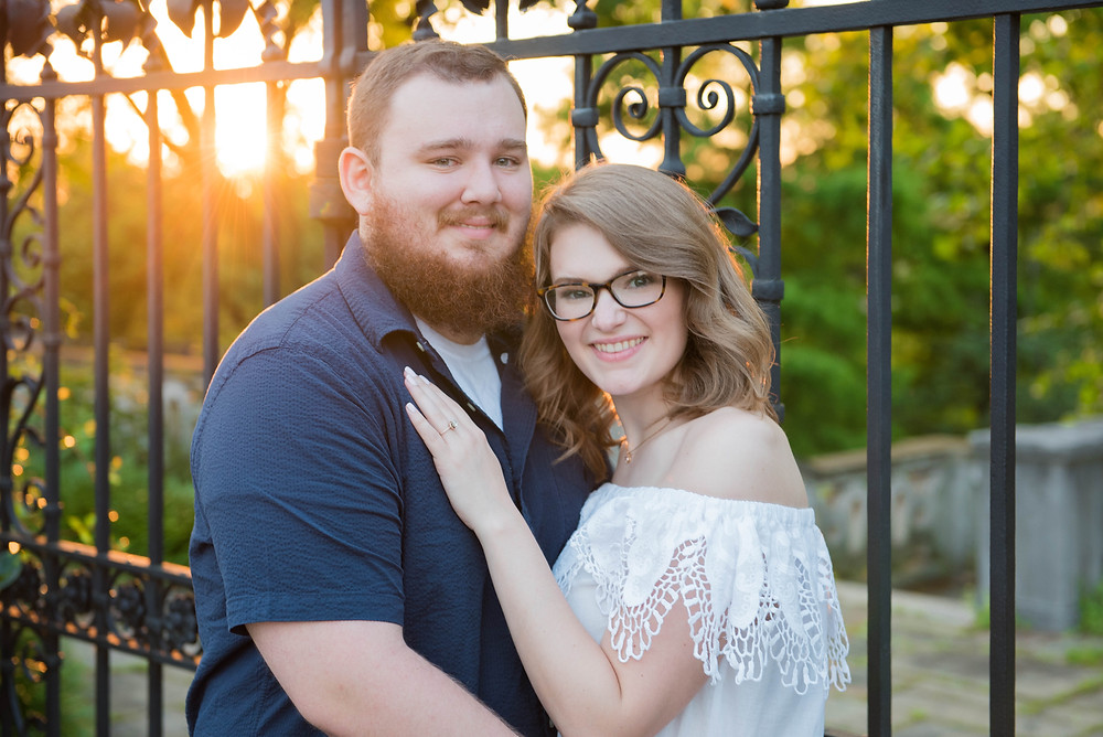 A couple posed standing together in front of an iron gate with gorgeous yellow sunlight behind them.