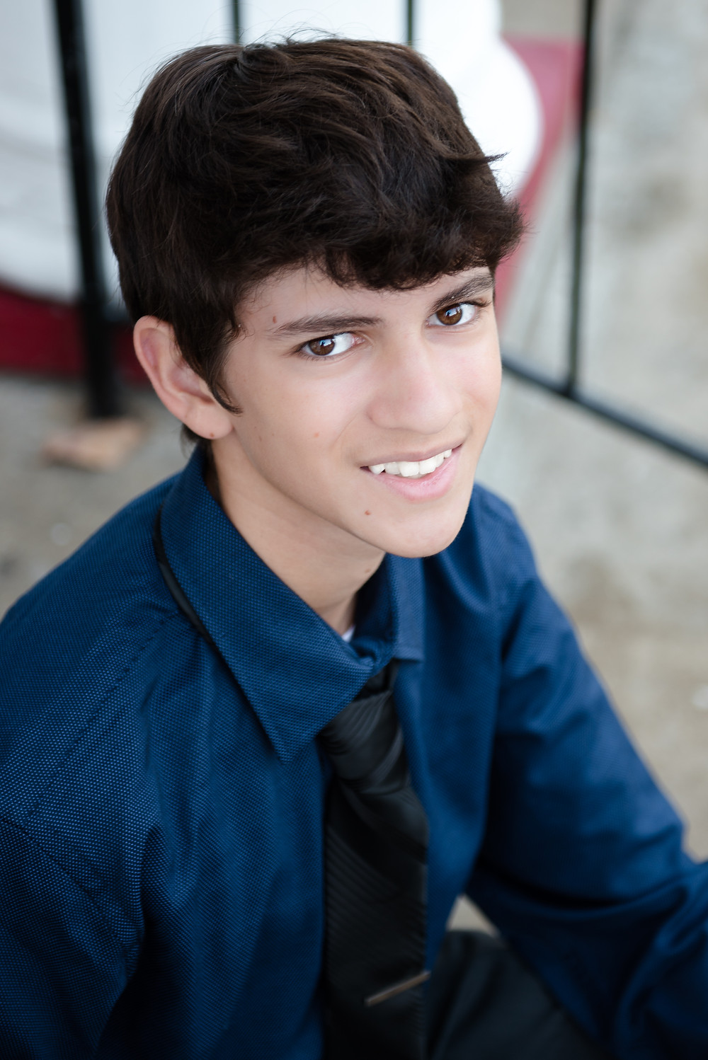 A portrait of a senior guy in a blue shirt and black tie during his photoshoot in Weirton, WV.