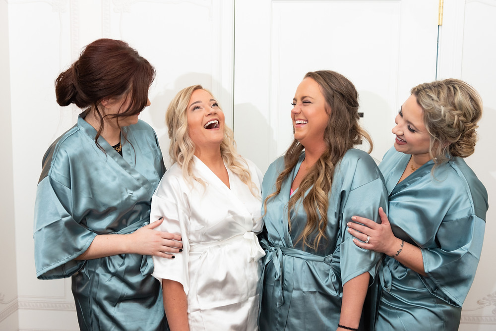 Bridesmaids in light blue robes laughing with the ride before the wedding