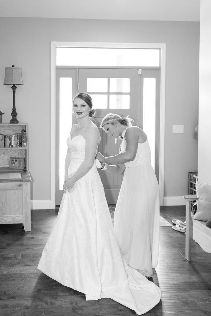 Black and white photo of the bride putting on her wedding dress