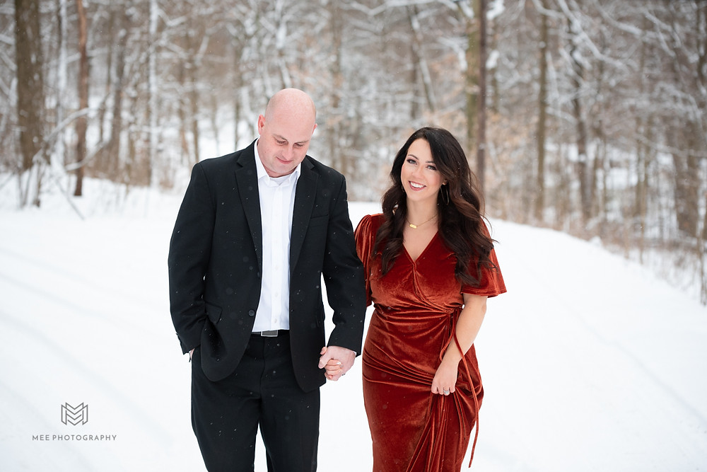 Engagement session in the snow with guy wearing black suit and girl wearing red velvet dress