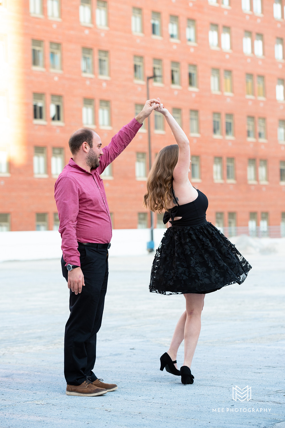 Couple dancing on rooftop during engagement session in Pittsburgh