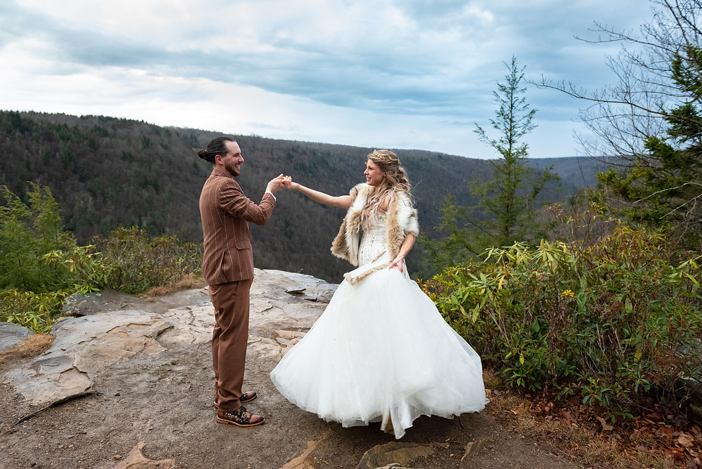 Groom wearing a brown suit sprinning bride at an overlook in West Virginia