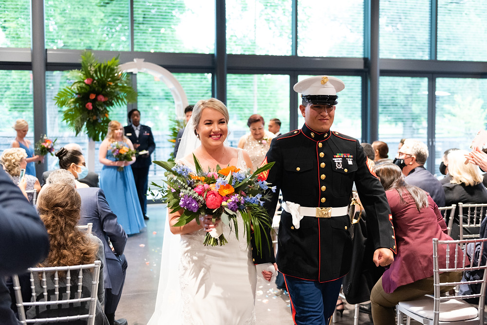 Bride and groom walking down the aisle after their wedding ceremony at the Aviary