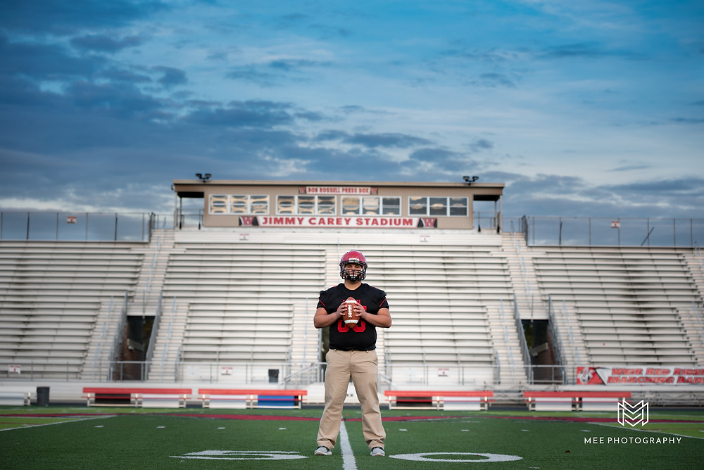 Senior guy holding the football on the 50 yard line of the football field with the bleachers in the background