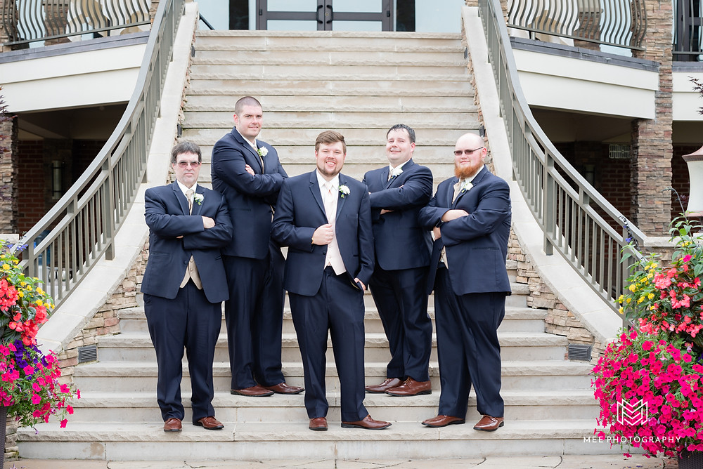 Groomsmen posed on stairs of The Lake Club in navy suits