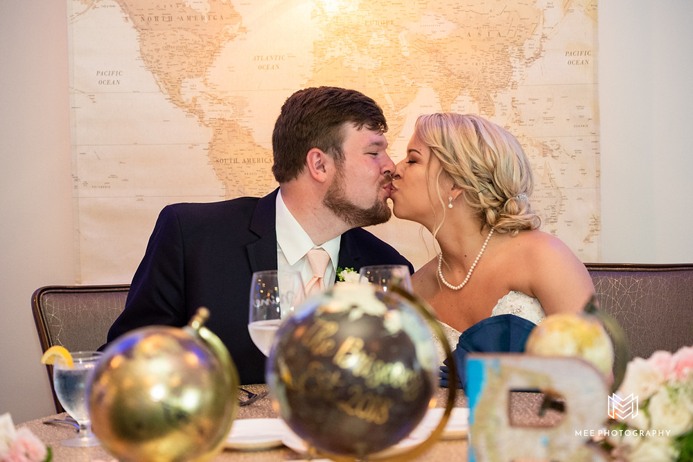 Bride and groom kiss at head table