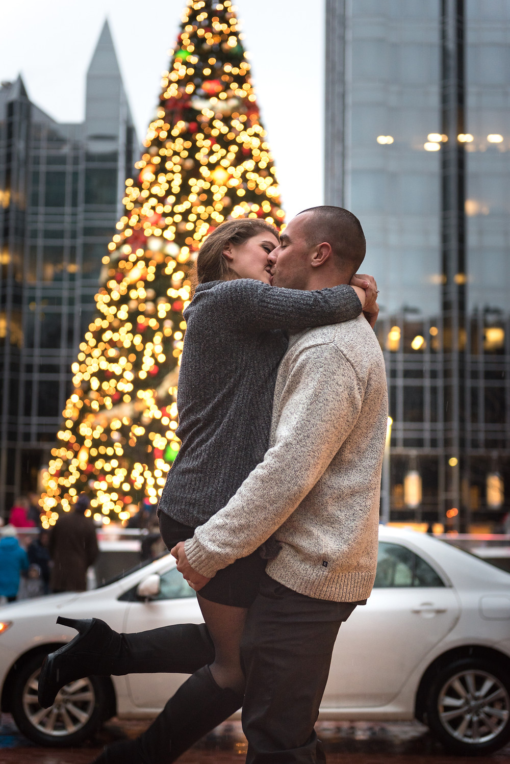 Guy holding girl close in front of the Christmas tree in Pittsburgh during their engagement session.