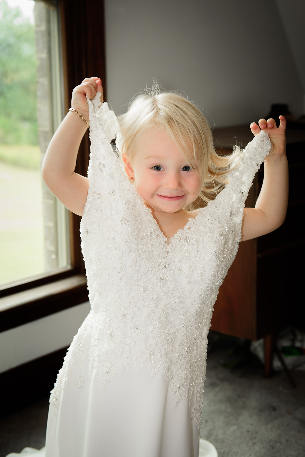 A very happy girl in her mom's wedding dress.