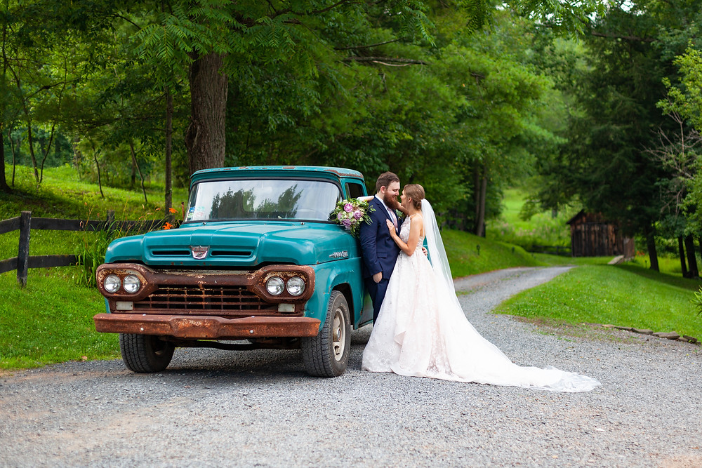 Bride and groom pose with a vintage blue Ford pickup truck