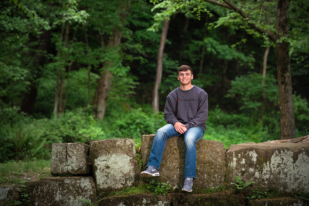 Senior guy sitting on rock wall in the woods at Tomlinson Run State Park