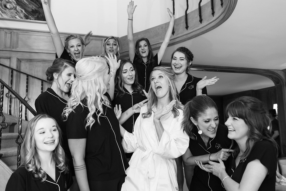 Bride and bridesmaids celebrating before the wedding on a spiral staircase