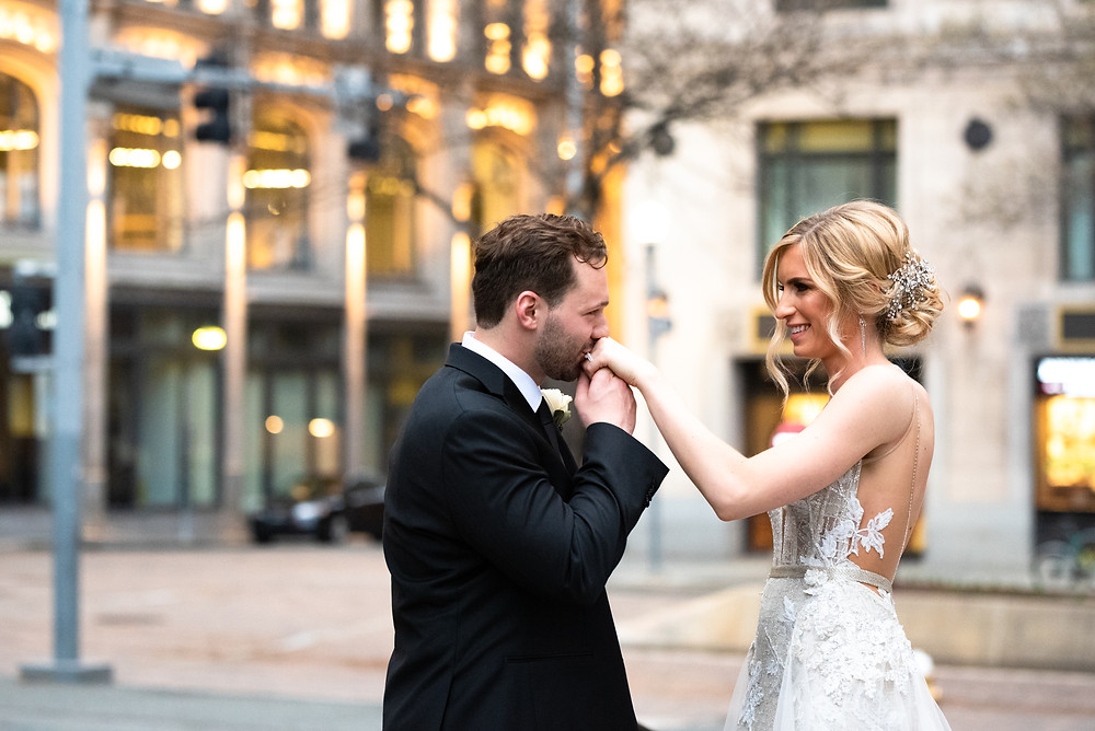 Groom kissing the bride's hand during portraits in Pittsburgh