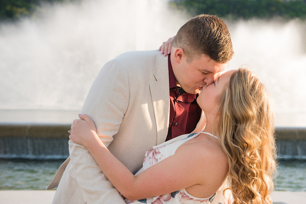 Couple kissing in front of the massive fountain at Point State Park with water spraying behind them