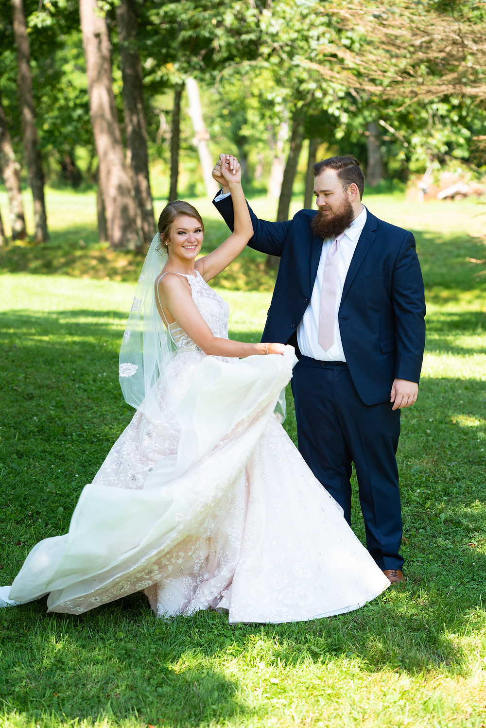 Groom spinning bride in a pink Hayley Paige dress