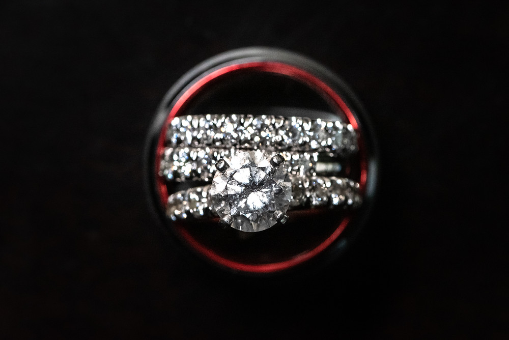 Diamond engagement ring inside of the groom's black and red wedding band