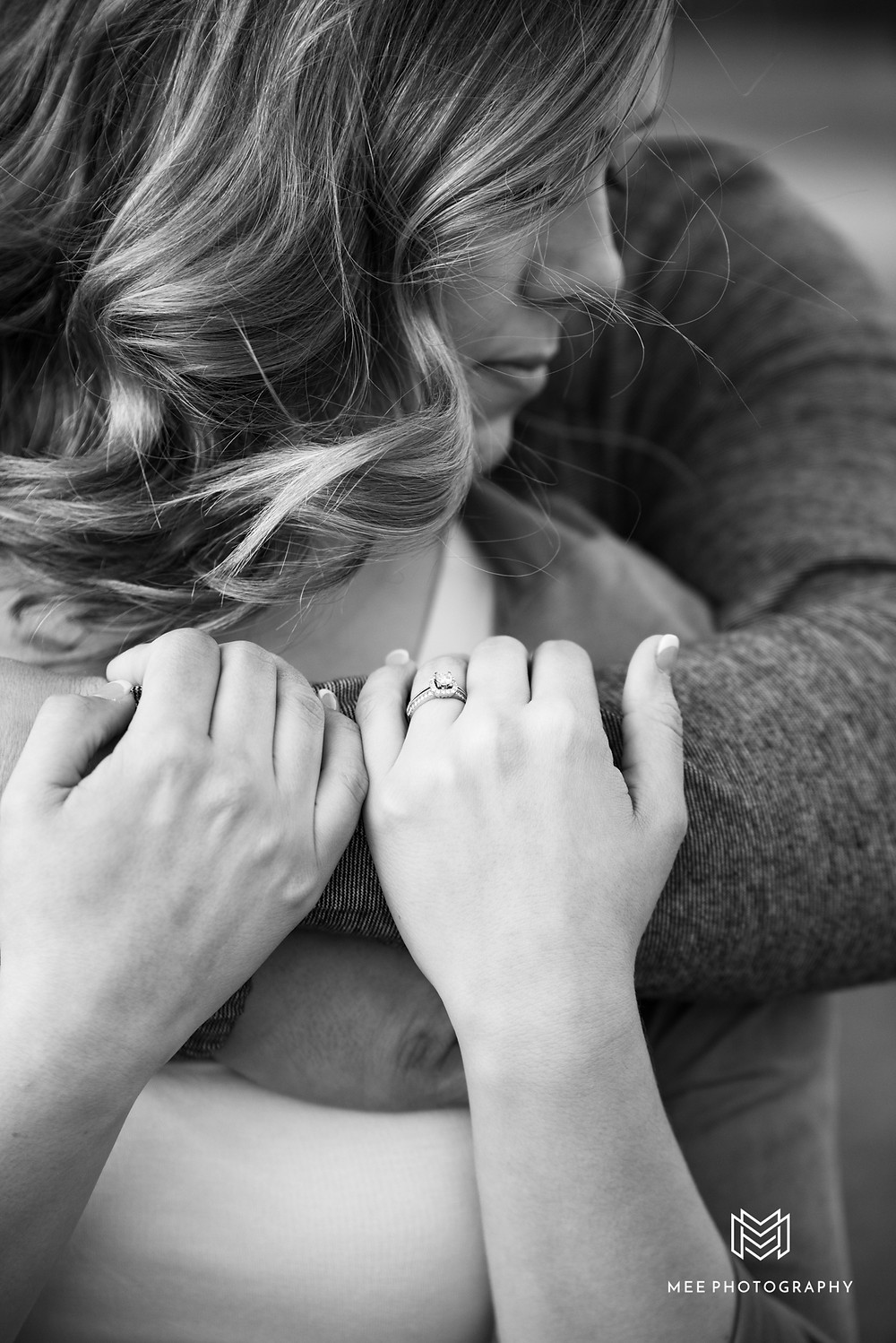 Romantic black and white engagement photo of couple embracing