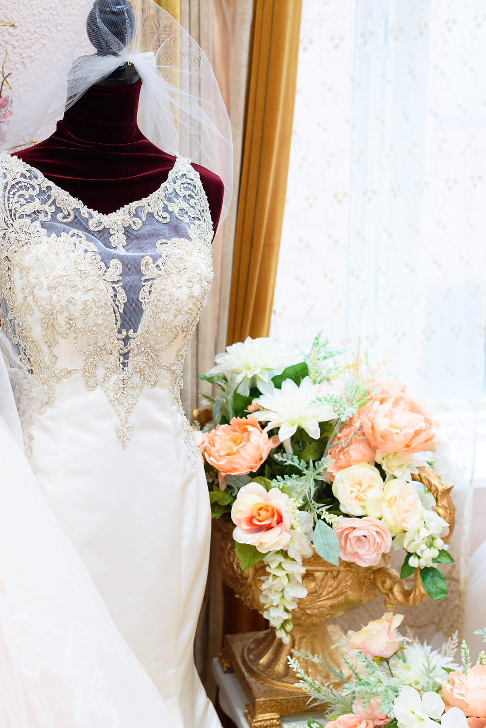 A beautiful beaded wedding dress on a maniquin at Babette's Gowns. Pictured with a veil and peach roses.