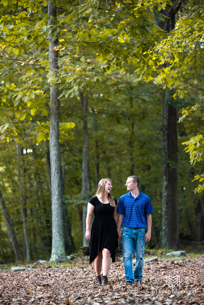 Couple laughing and walking through the woods at Valley Falls State Park in Fairmont, West Virginia