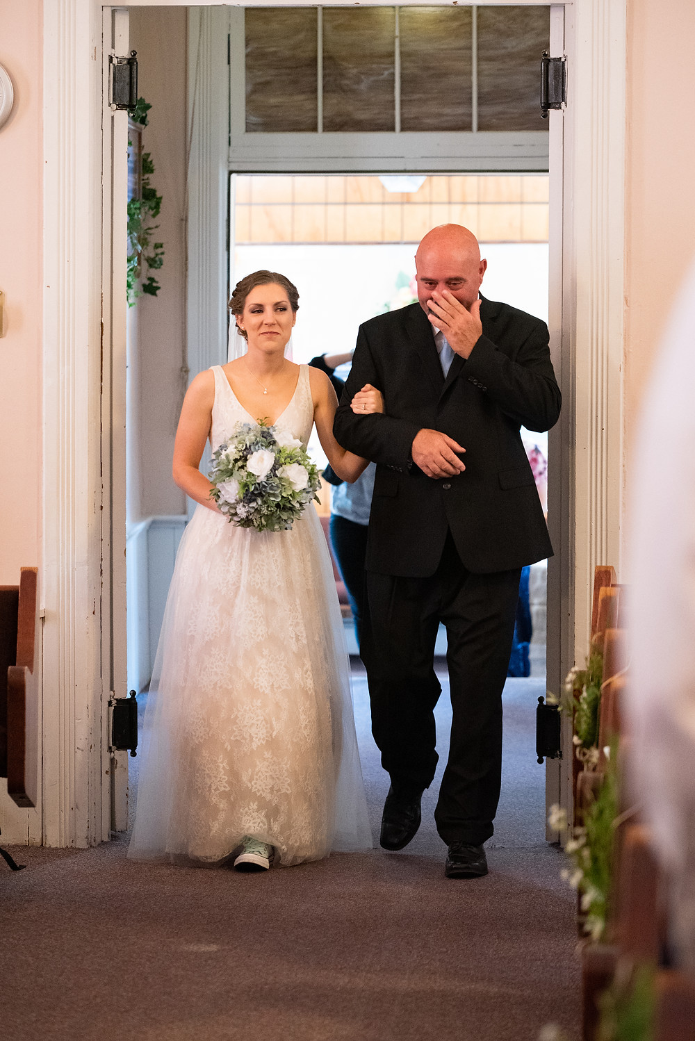 Dad walking daughter down aisle and wiping tears at Hookstown Free Methodist Church