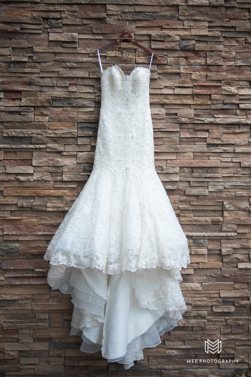Photograph of a memaid style wedding dress hangin on the stone wall of the Lake Club