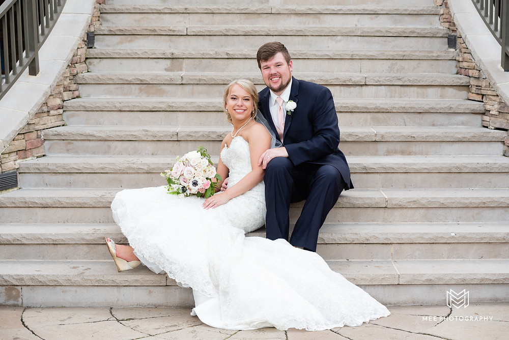 Bride and groom sitting on the stairs of The Lake Club