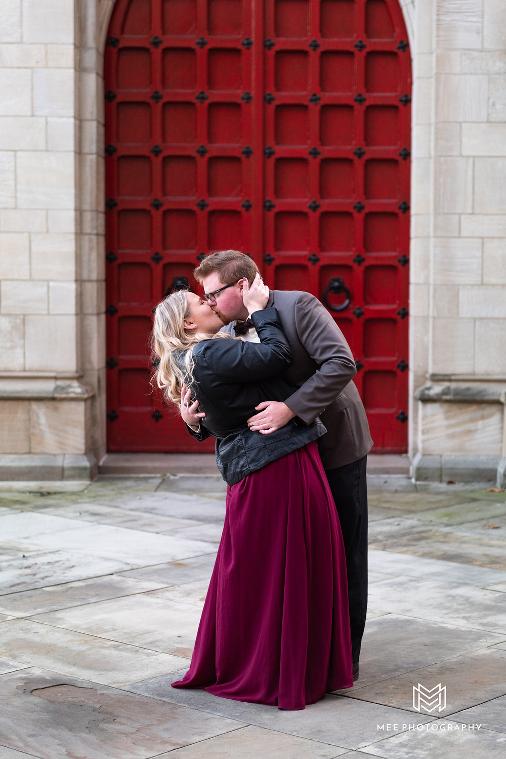 Couple kissing in front of red door at Pitt Cathedral during their engagement photos