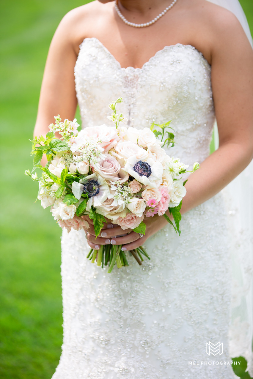 Detail shot of bride's necklace and bouquet