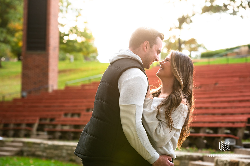 Couple laughing on the stage at Oglebay Park in Wheeling during their engagement photoshoot
