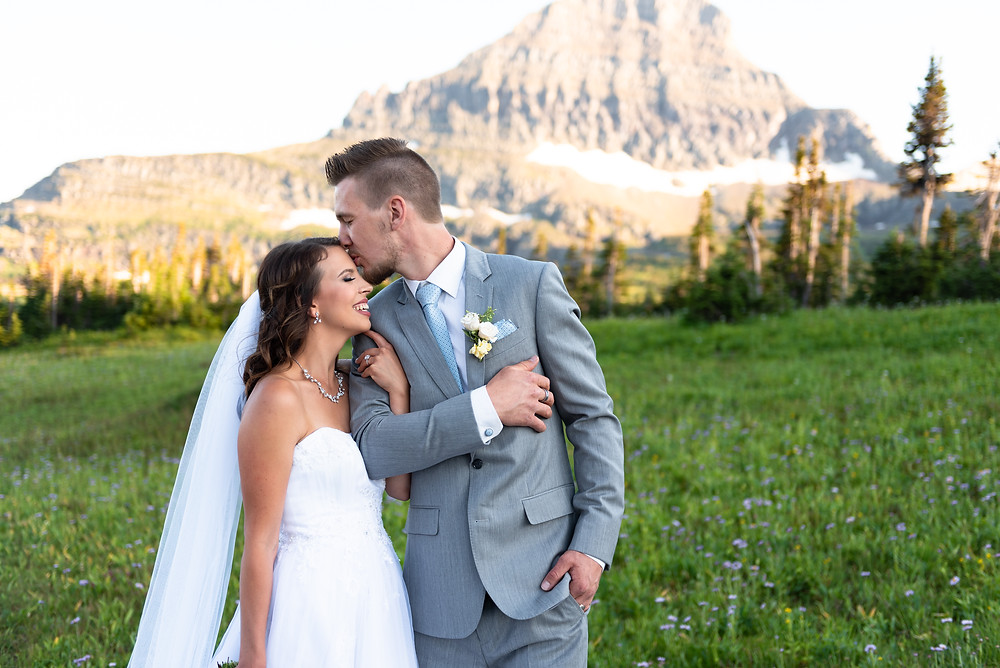 Groom kissing bride on the forehead with the mountains of Glacier National Park in the Background