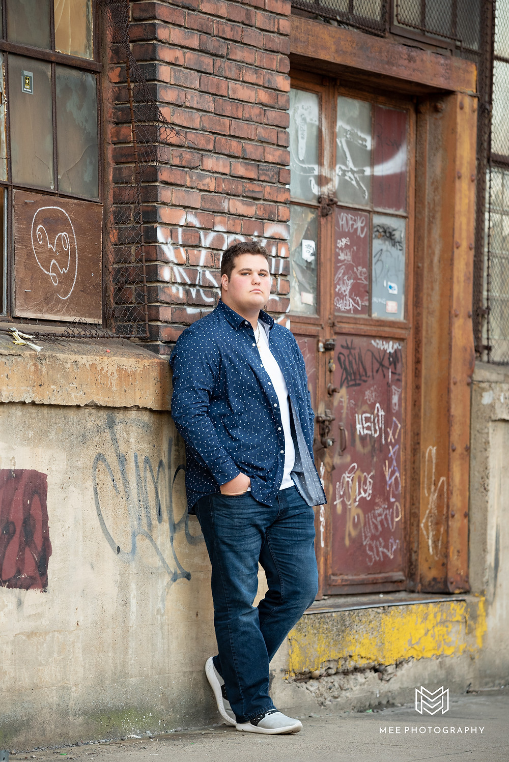 High school senior guy photography in the Strip District of Pittsburgh in front of old buildings and grafitti