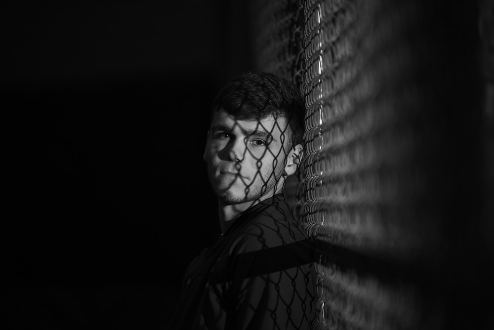 Senior session at night with boy leaning on the fence