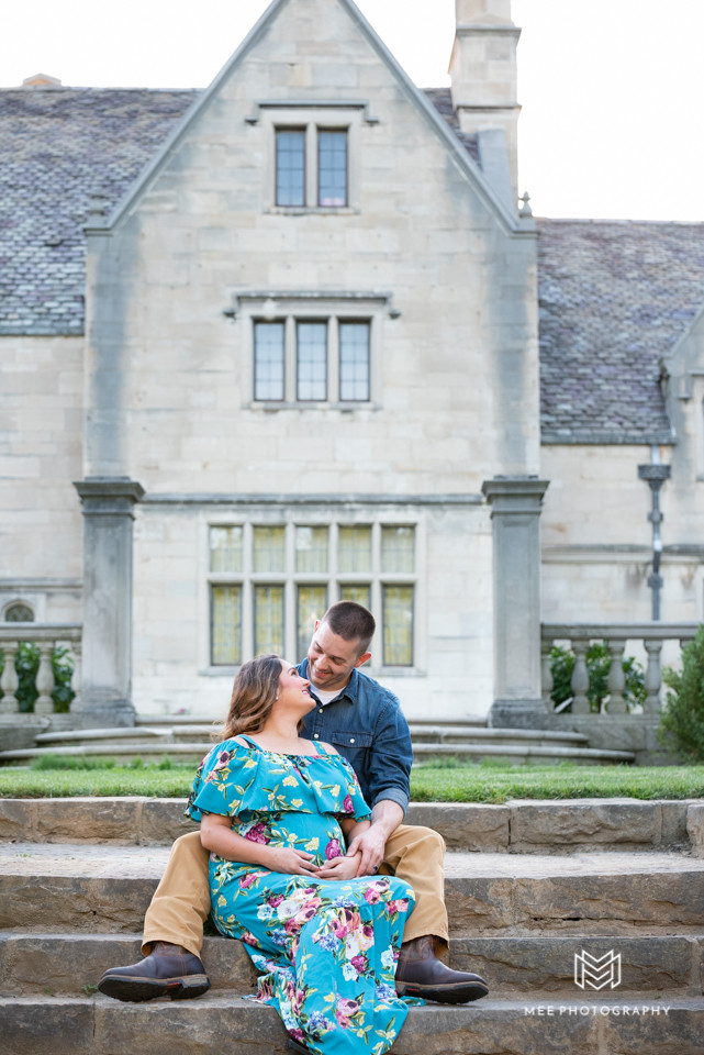 Pregnant wife and husband sitting on the steps of the Hartwood Acres Mansion