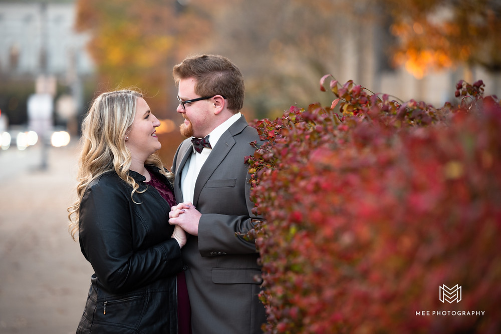Couple wearing formal attire posed against red bushes during their engagement session in Pittsburgh