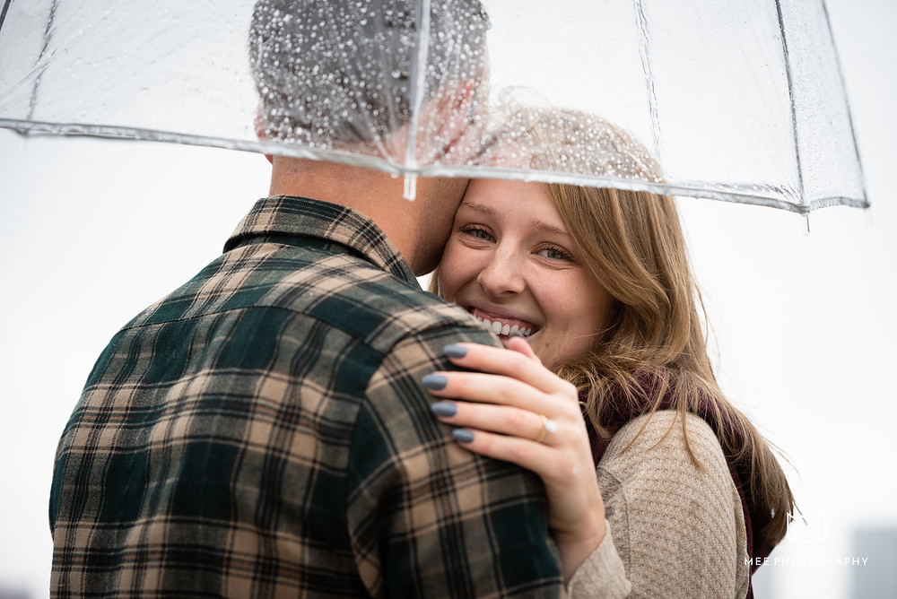 Newly engaged couple hugging under a clear umbrella in the rain on the Mount Washington Overlook