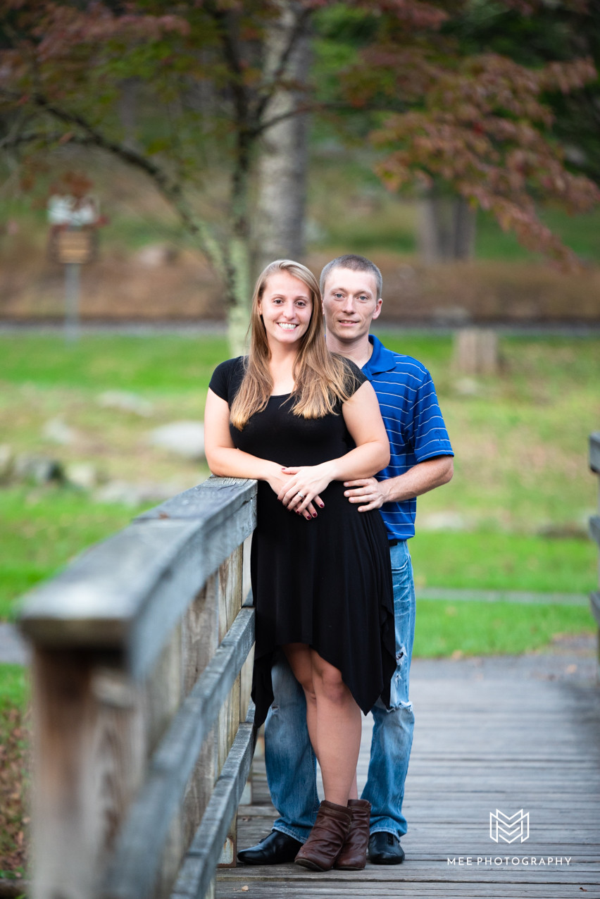 Fall engagement session with couple standing on bridge in Fairmont, WV