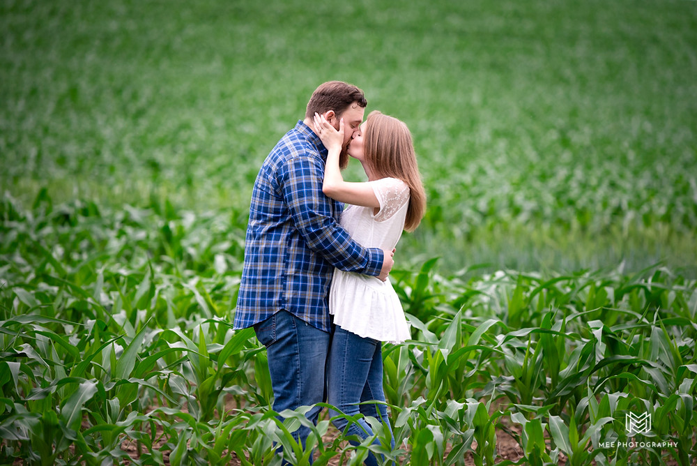 Engagement photography session in a corn field at Chanteclaire Farm. The couple is kissing.
