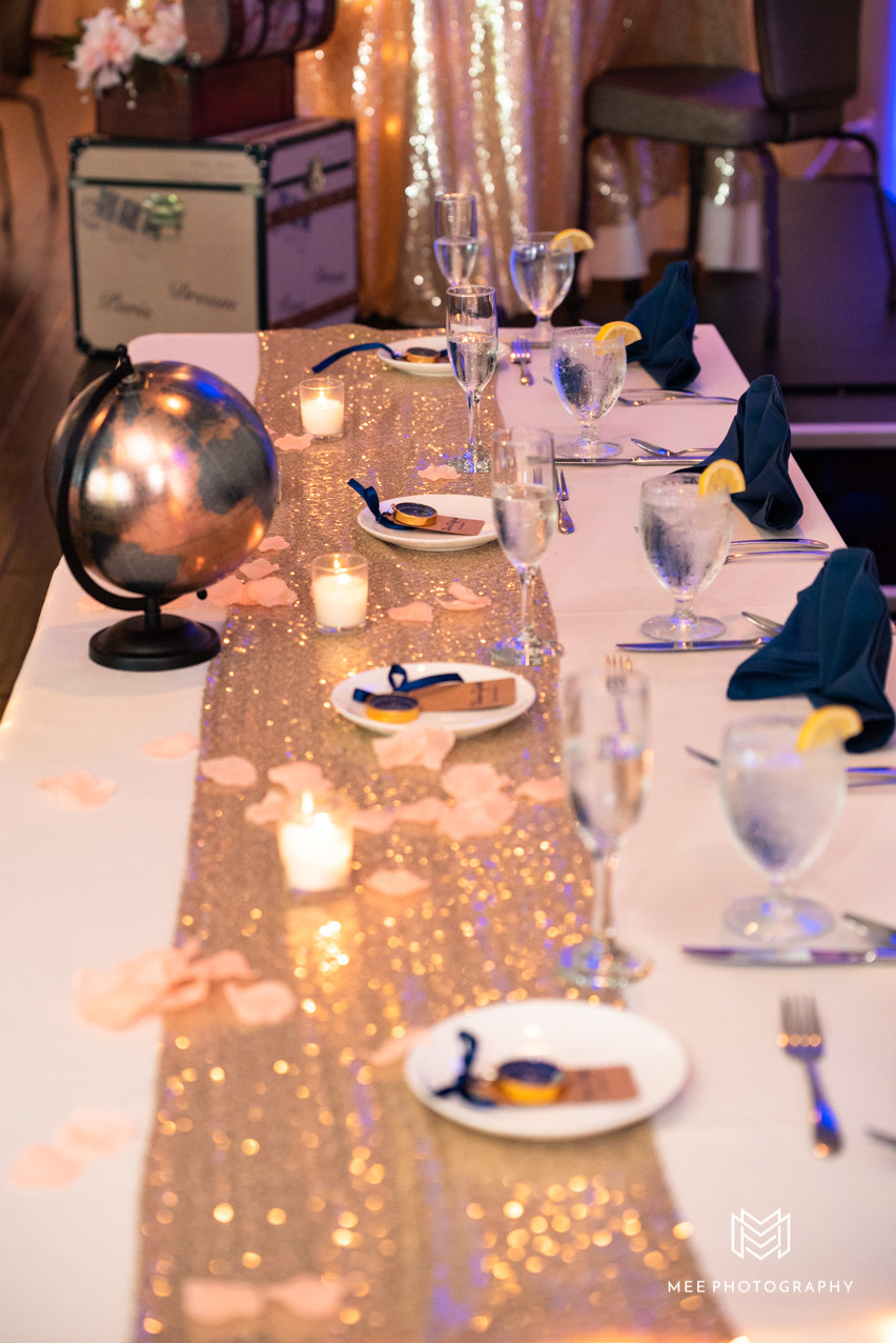 travel theme wedding with trunks and gold sequin table runner