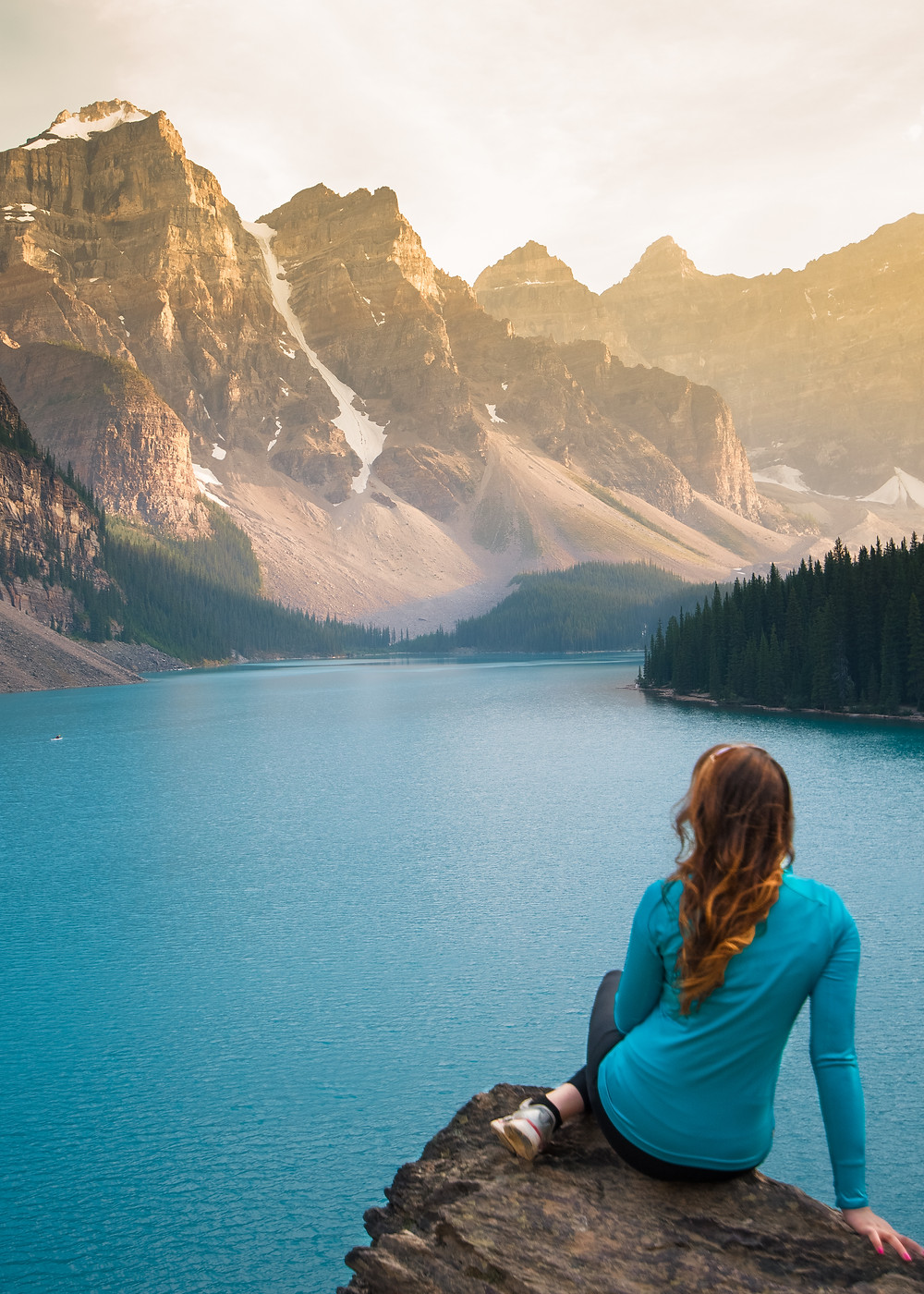 A girl sitting on a rock watchin the sunset at Moraine Lake in Banff, Canada.