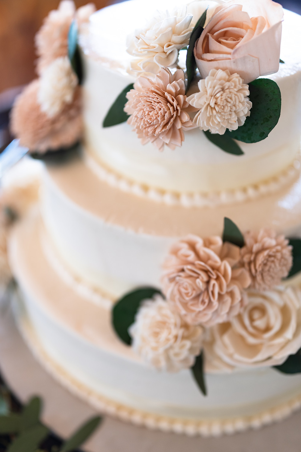 Three tiered white wedding cake decorated with blush wood flowers