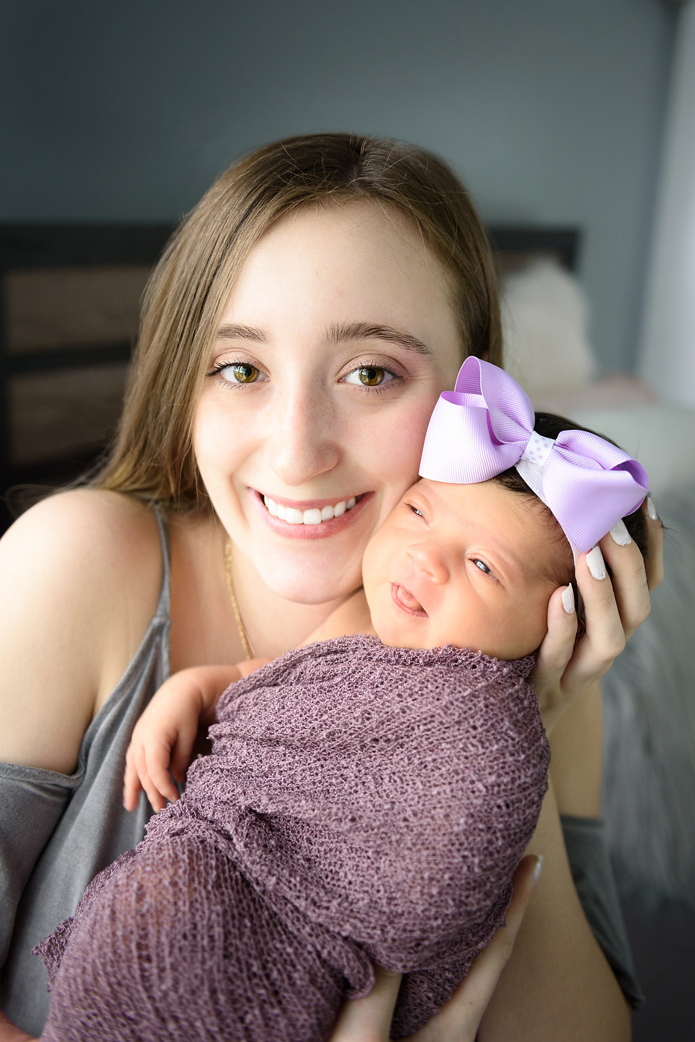 Newborn curious about the world while her mom smiles for a picture