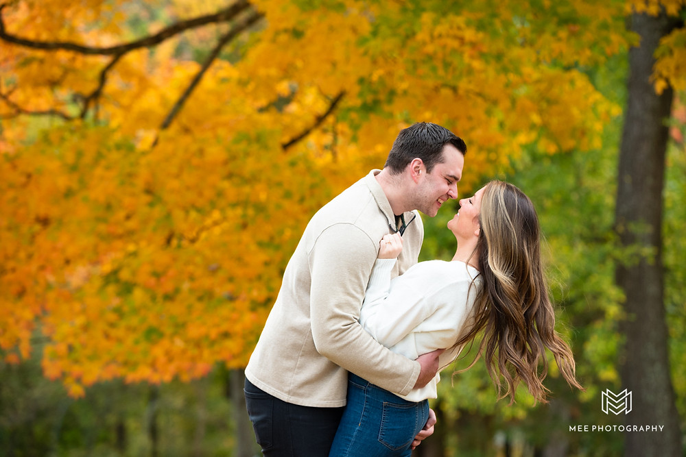 Couple wearing cream colored sweaters and jeans during their fall engagement session at Oglebay Mansion