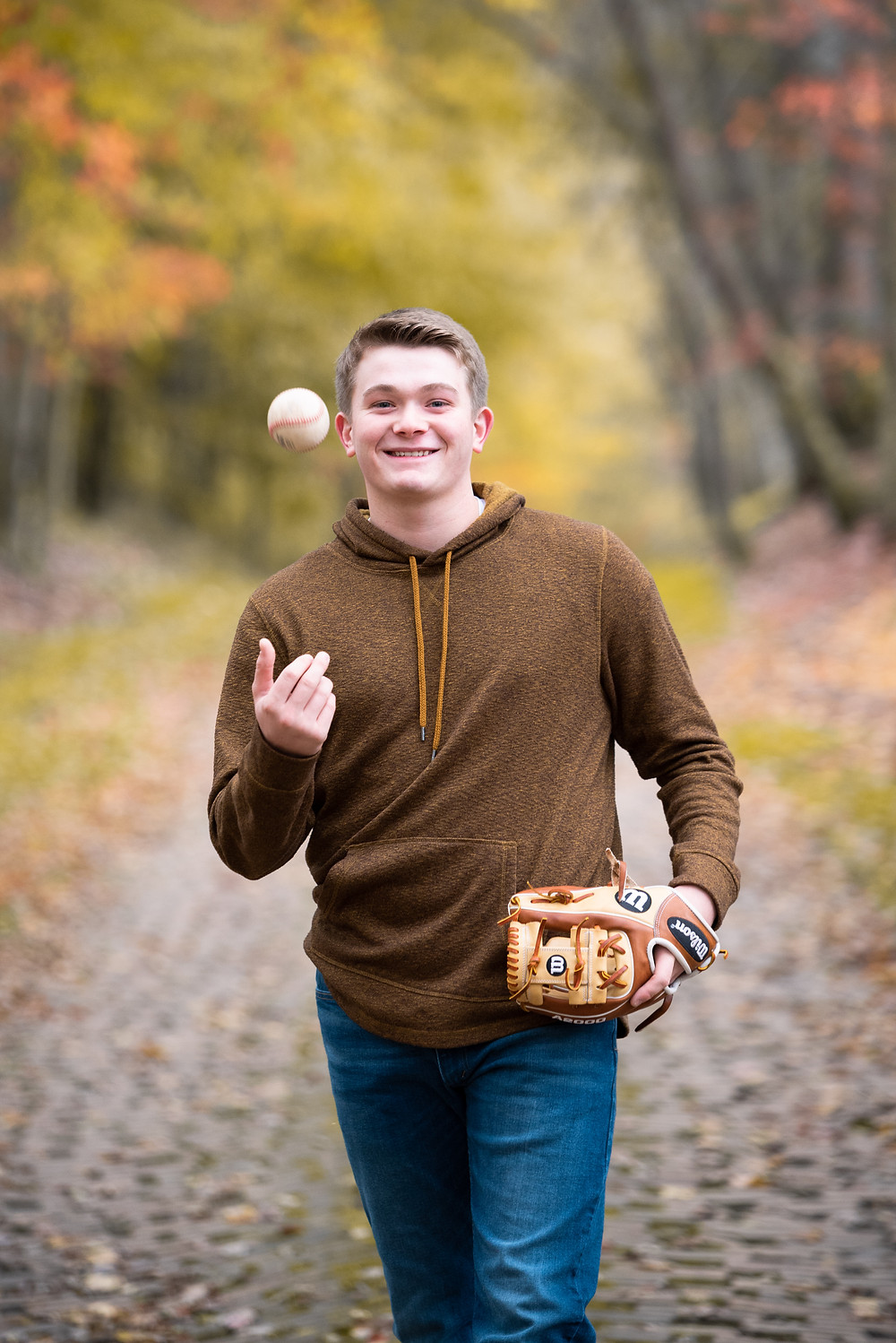 Senior guy fall photography session with him walking and throwing a baseball
