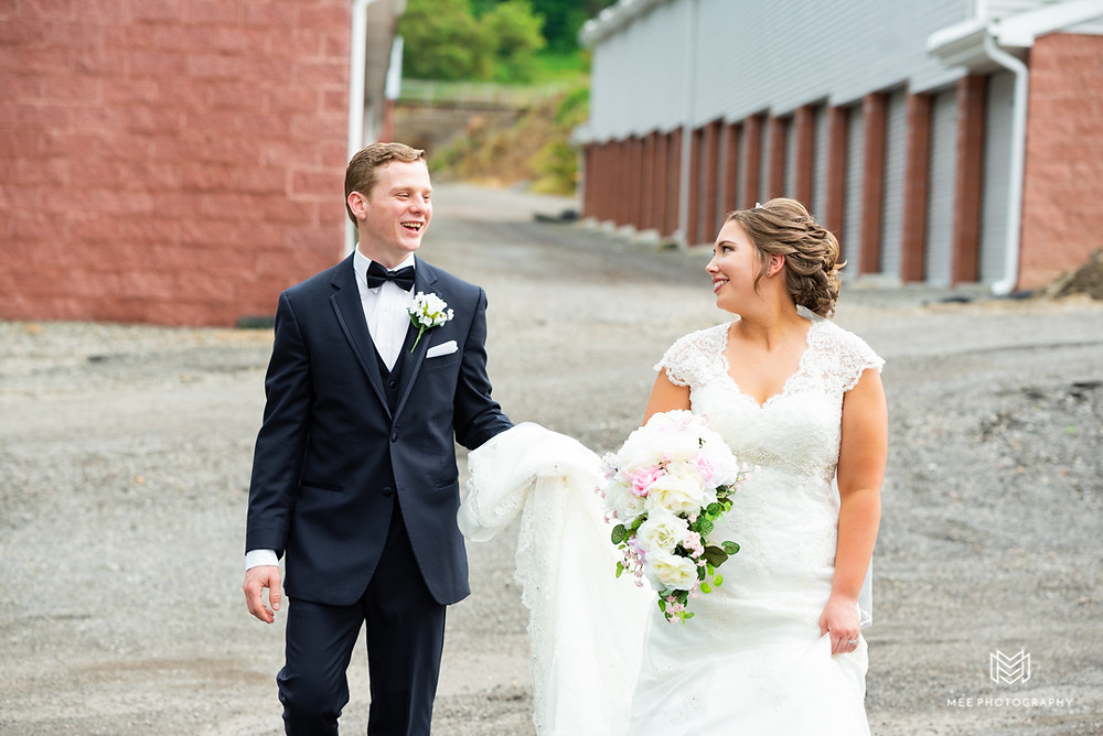 Groom helping bride carry her dress through the parking lot