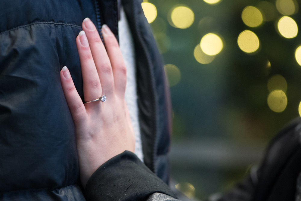 Ring shot of bride's hand on groom's chest and christmas lights in the background