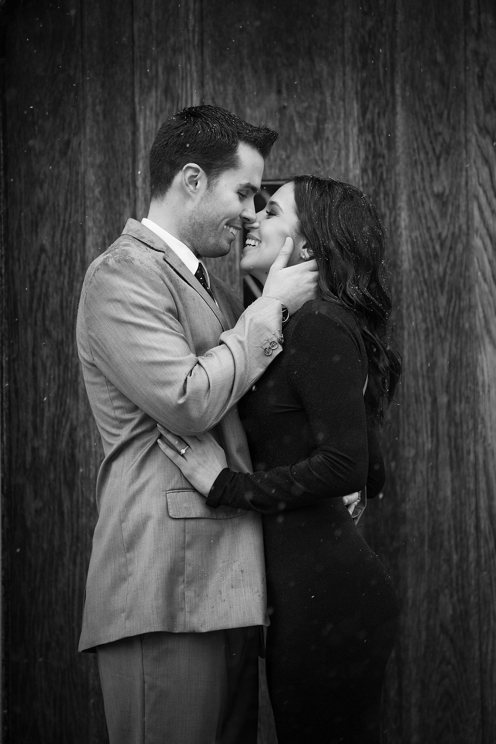 Black and white engagement photo of couple going in for a kiss