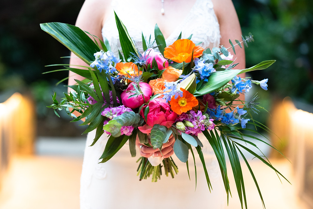 Colorful bridal bouquet with bright pink, orange, and purple flowers