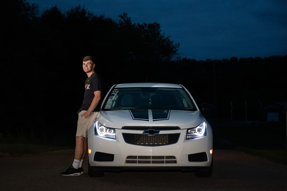 Night photography of a senior leaning against his white chevy cobalt